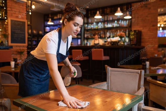 Pretty young waitress in apron using detergent and duster to clean table