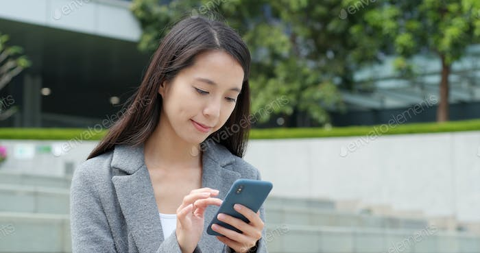 Businesswoman use of smart phone in city