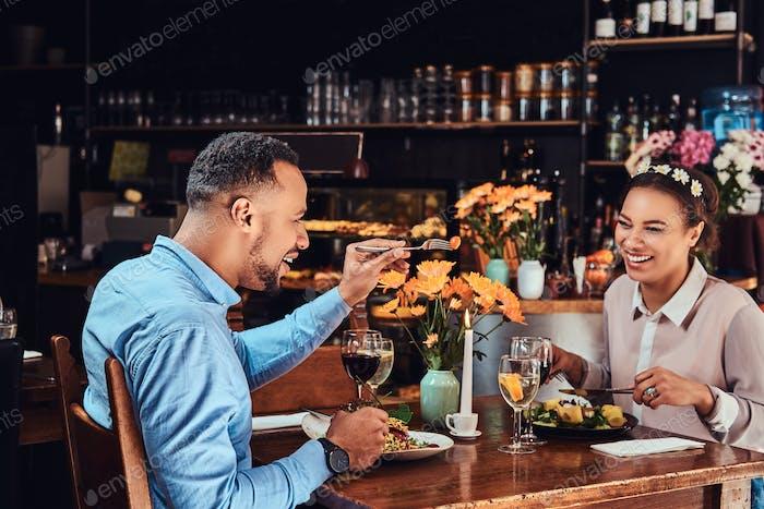 Glückliches schönes afroamerikanisches Paar in der Liebe mit einer tollen Zeit zusammen in einem Restaurant