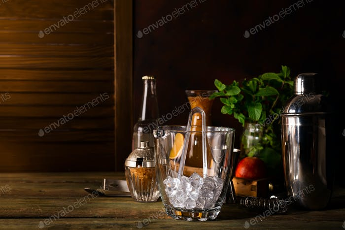 Glass ice bucket and Different cocktails in glass with Bar accessories isolated on black