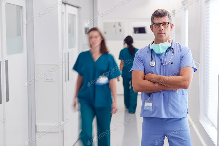 Portrait Of Mature Male Doctor Wearing Scrubs Standing In Busy Hospital Corridor