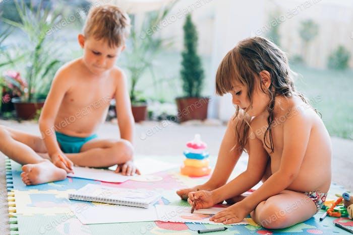 Kleiner Junge und Mädchen Zeichnung mit Buntstiften