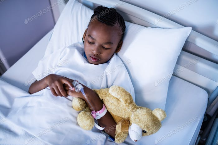 Patient sleeping with teddy bear on the bed at hospital