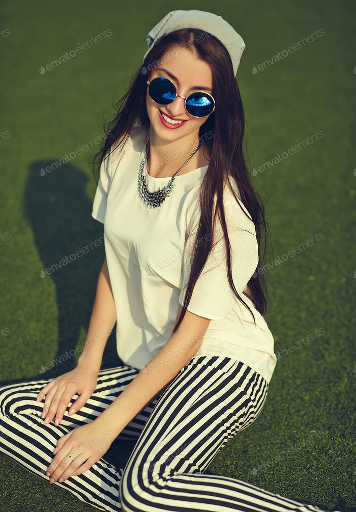 Portrait of young stylish woman sitting on the grass