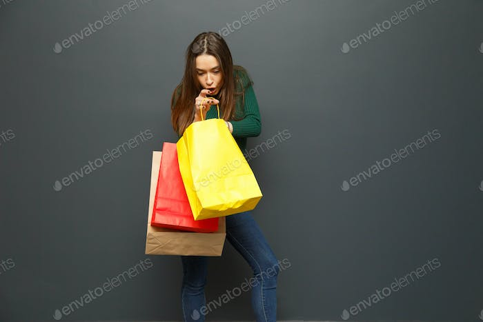 Woman looking in amazement at her shopping bags.