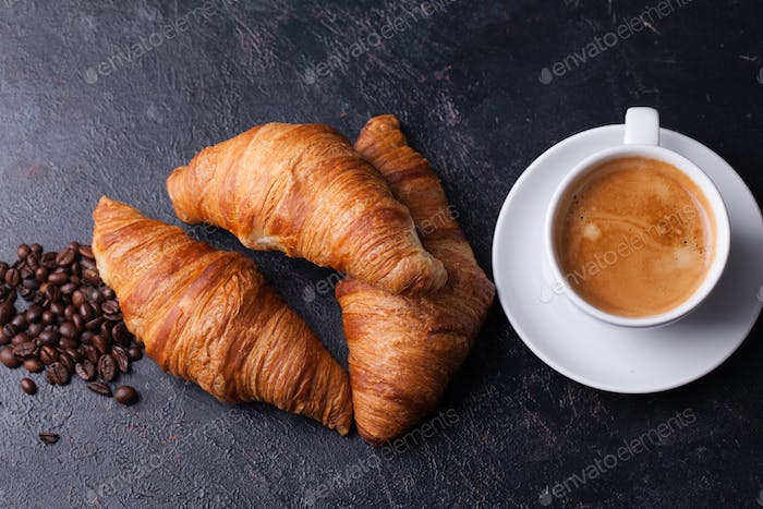 Croissants with cup of coffee and coffee beans on dark wooden table