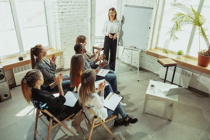 Female caucasian speaker giving presentation in hall at university or business centre workshop