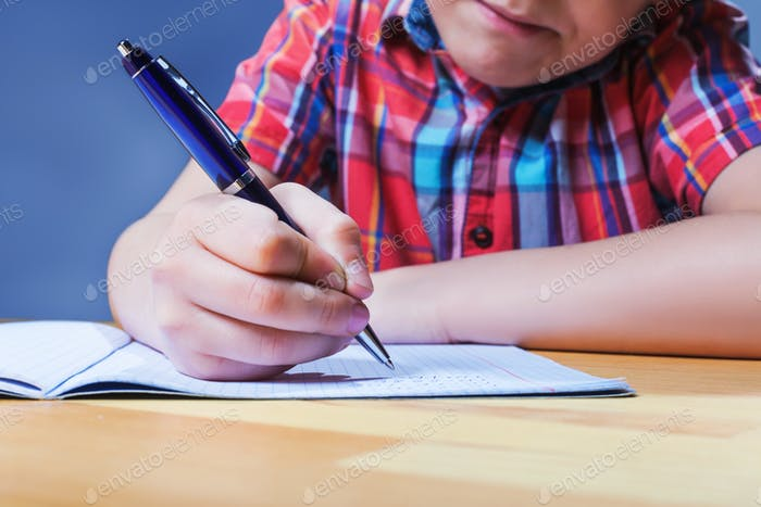 Pupil at the desk writing in notebook closeup view