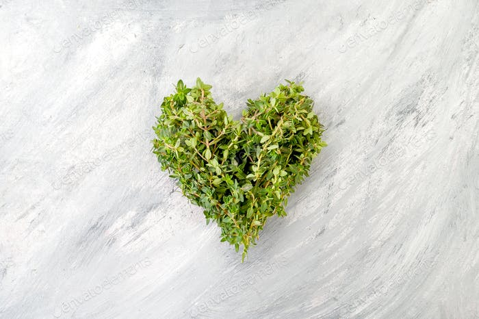 Heart of fresh thyme on a light old scratching table.