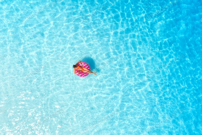 Aerial view of a young woman swimming with the donut swim ring