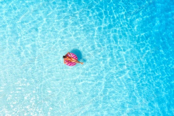 Luftaufnahme einer jungen Frau schwimmen mit dem Donut Schwimmring