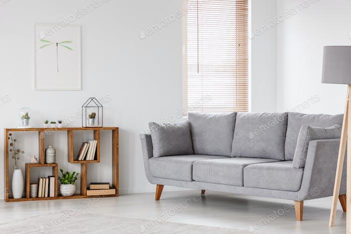Echtes Foto von einem Skandi Wohnzimmer Interieur mit grauen Sofa sta