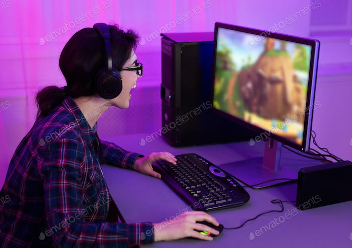 Addicted female gamer playing game online on computer