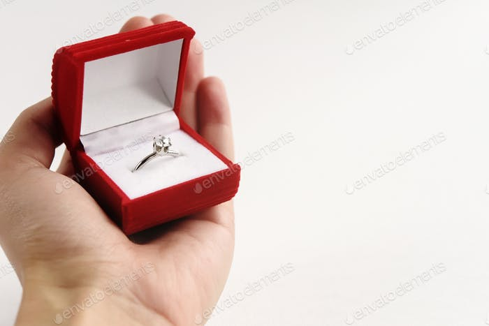 luxury ring with diamond in stylish red box in hand on white background