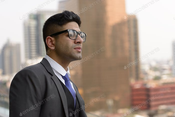 Portrait of young handsome Indian businessman in the city