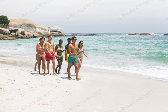 Front view of diverse group of friends walking and enjoying on beach on a sunny day