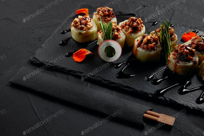 delicious sushi roll with creamy eel and kimchi mayonnaise on slate board and chopsticks