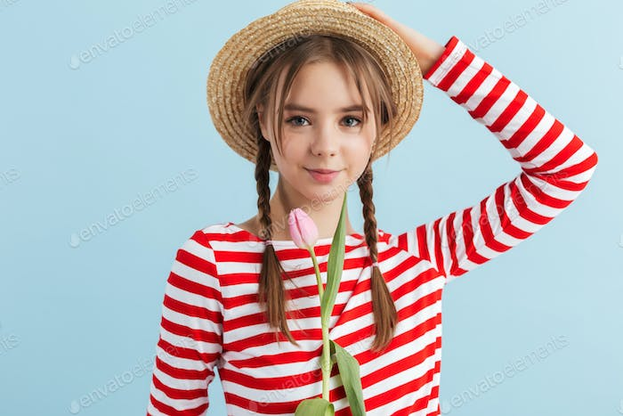 Young cute girl in straw hat and striped vest holding pink tulip flower looking in camera