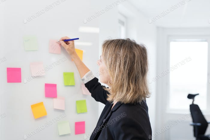 Architect writing on whiteboard in office