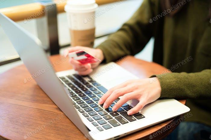Frau Verwendung von Notebook-Computer mit Kreditkarte für Online-Shopping