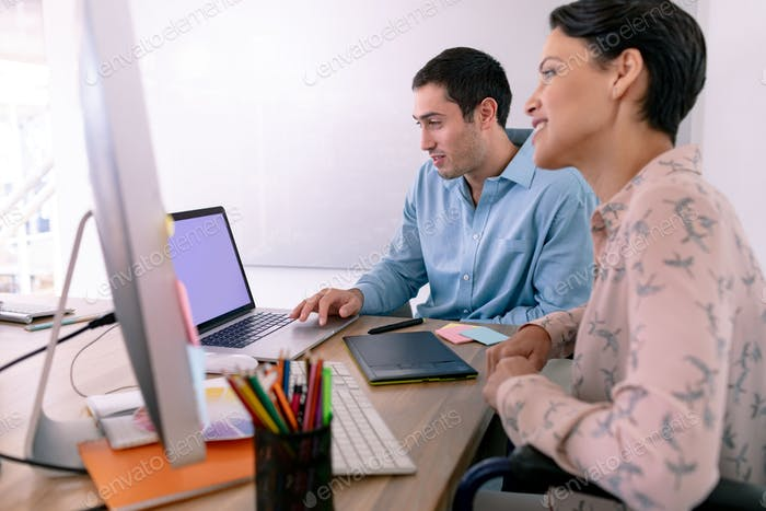Side view of diverse graphic designers working together at desk in a modern office
