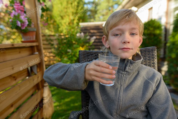Young handsome boy with glass of water sitting in the backyard