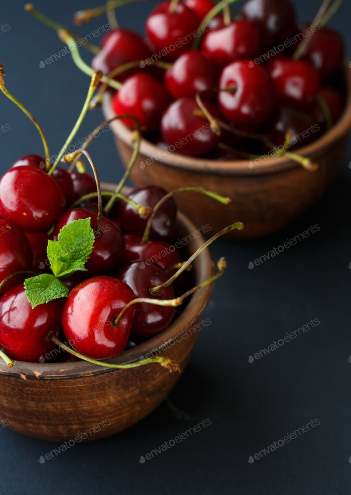 Ripe cherries in a clay bowl on black background