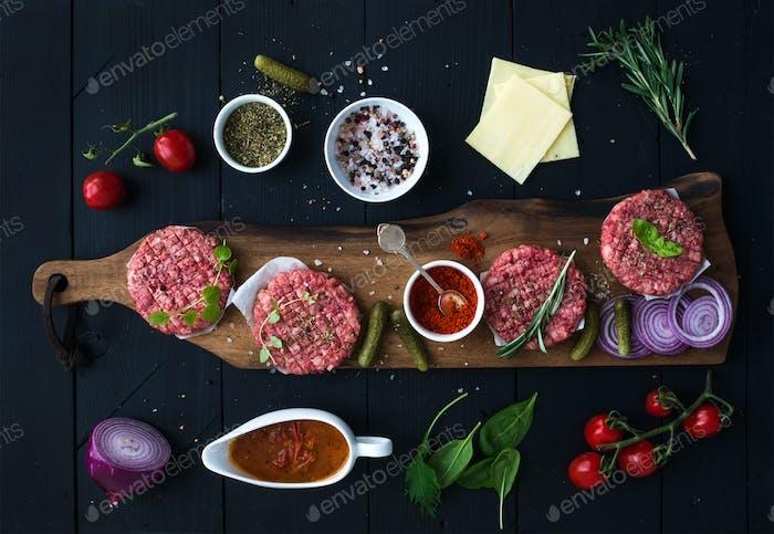 Zutaten zum Kochen von Burgern. Rohhackfleisch Schnitzel auf Holzschneidebrett