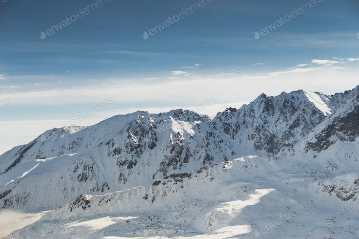 Wide shot aerial view of snow capped cold rock mountains with sunny blue skies.