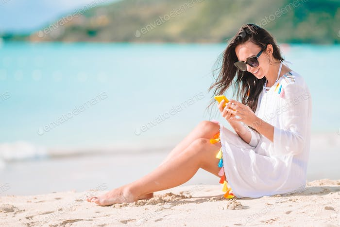 Young woman with smartphone during tropical beach vacation