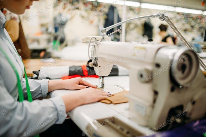 Schneiderhände näht Stoffe an einer Nähmaschine