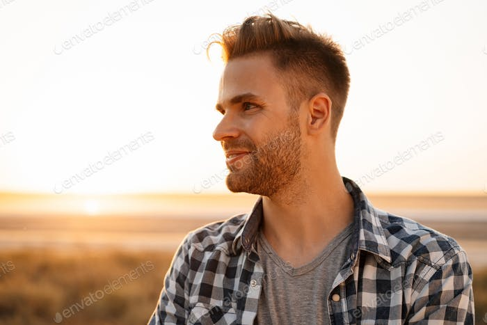 Handsome happy guy smiling and looking aside on nature at summer