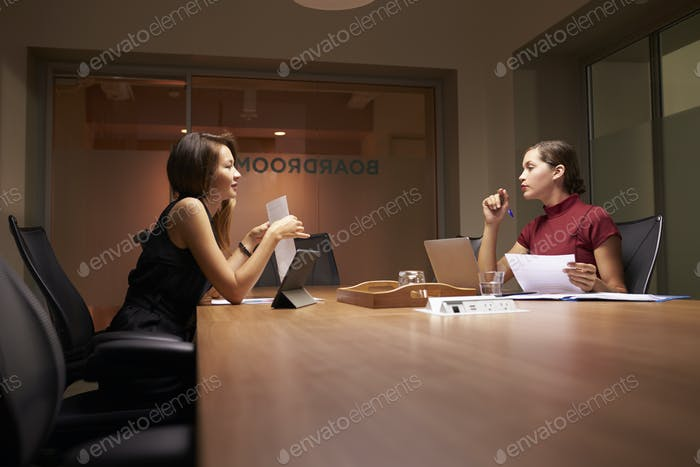 Two female business colleagues working late in an office