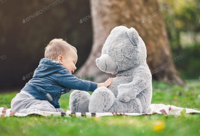 Best of friends. Cute toddler playing outdoors with his teddy bear