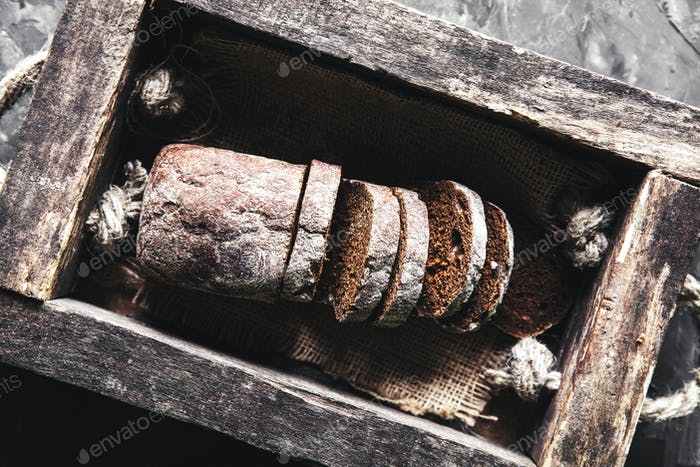 bread in an old wooden box already cut into pieces. food