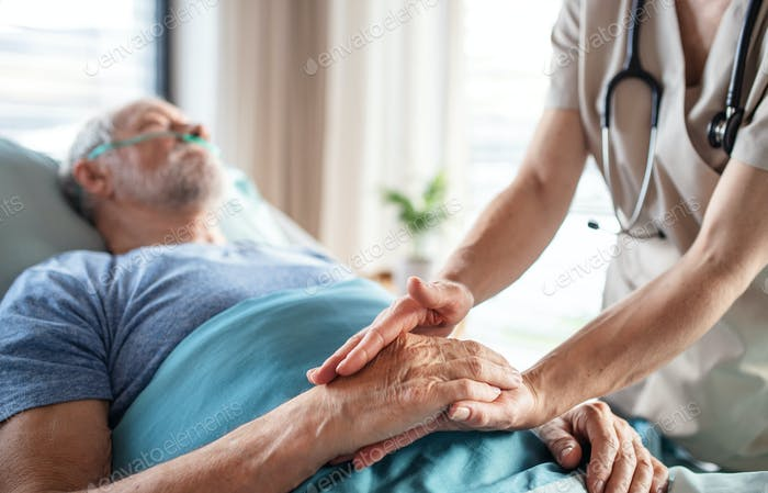 Unrecognizable female doctor examining senior man in bed in hospital.