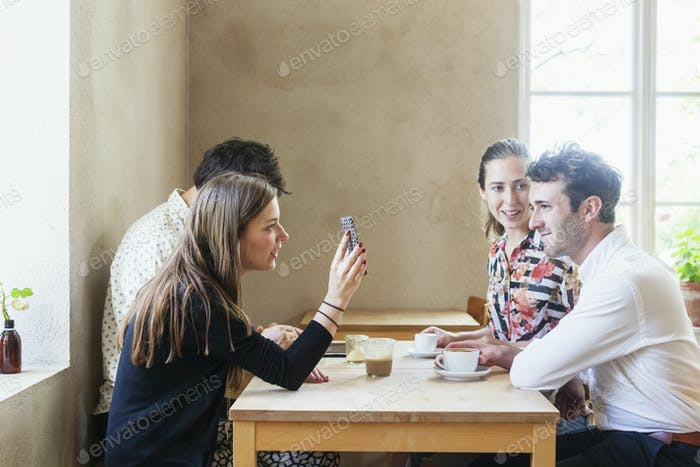 Young colleagues taking coffee break at restaurant