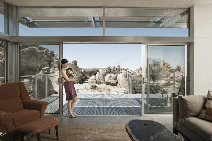A woman and a young child in the living space of an eco house in the desert.