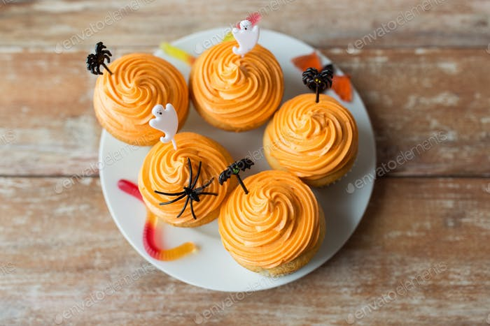 halloween party cupcakes with decorations on plate