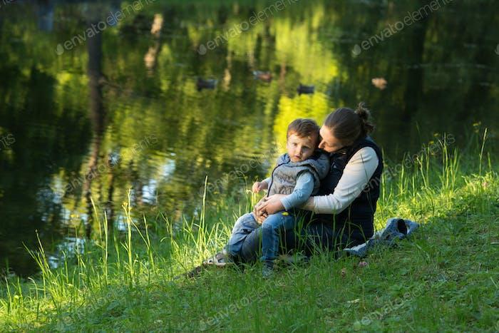 Familie. Junge schwangere Frau mit ihrem kleinen Sohn im Park. Park im Sommer. Dreharbeiten im Freien