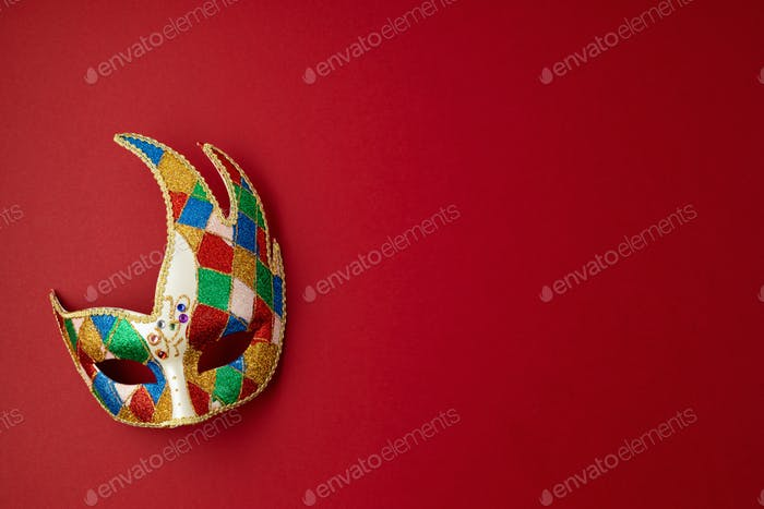 Festive, colorful mardi gras or carnivale mask and accessories over purple background