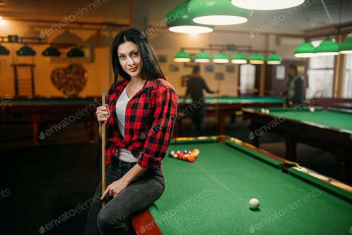 Female billiard player with cue poses at the table