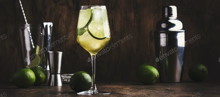 Mojito cocktail with lime and mint in wine glass