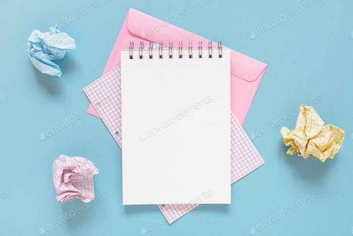 Blue Workplace with Open Notepad and Crumpled  Sheets of Paper