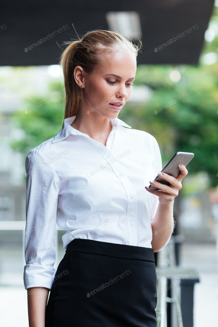 Blonde businesswoman texting message while standing outdoors