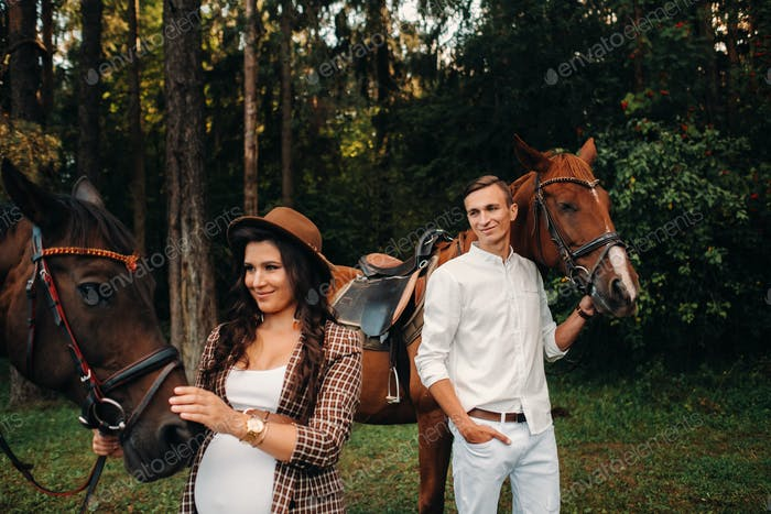 a pregnant girl in a hat and a man in white clothes stand next to horses in the forest in nature