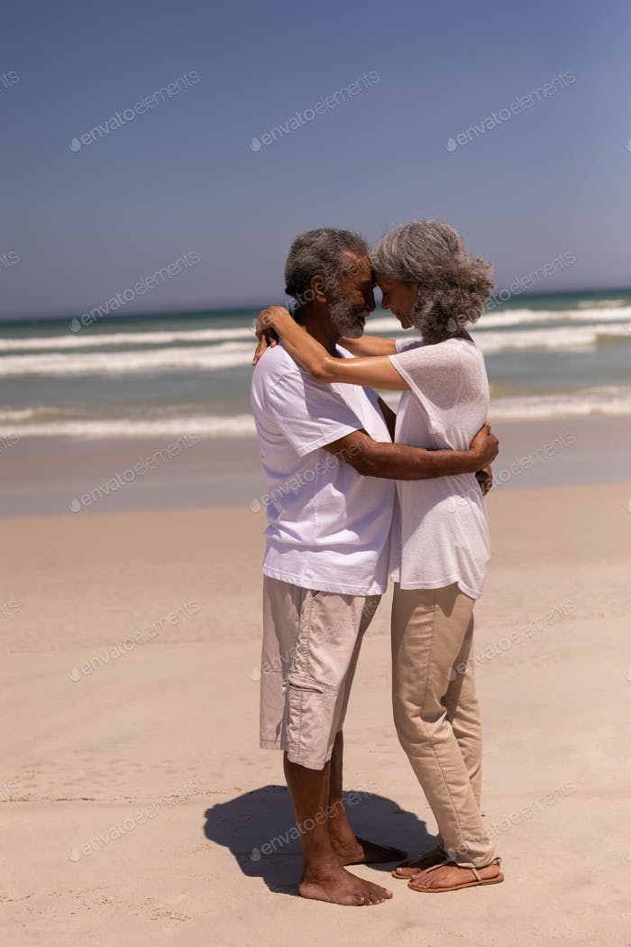 Side view of happy senior couple head to head and embracing