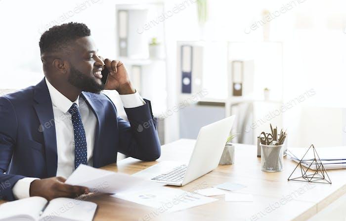 Lächelnd schwarz Geschäftsmann überprüft Berichte, Telefongespräche mit Assistent