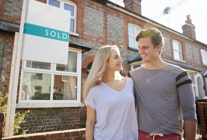 Excited Couple Standing Outside New Home With Sold Sign