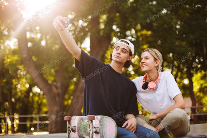 Smiling girl with headphones and young guy with skateboard happi
